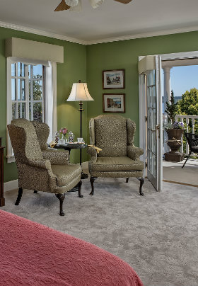 Wingback chairs in front of french doors opening to veranda