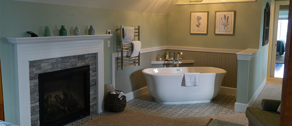 View of tub and fireplace in bathroom corner with decorative towel rack.