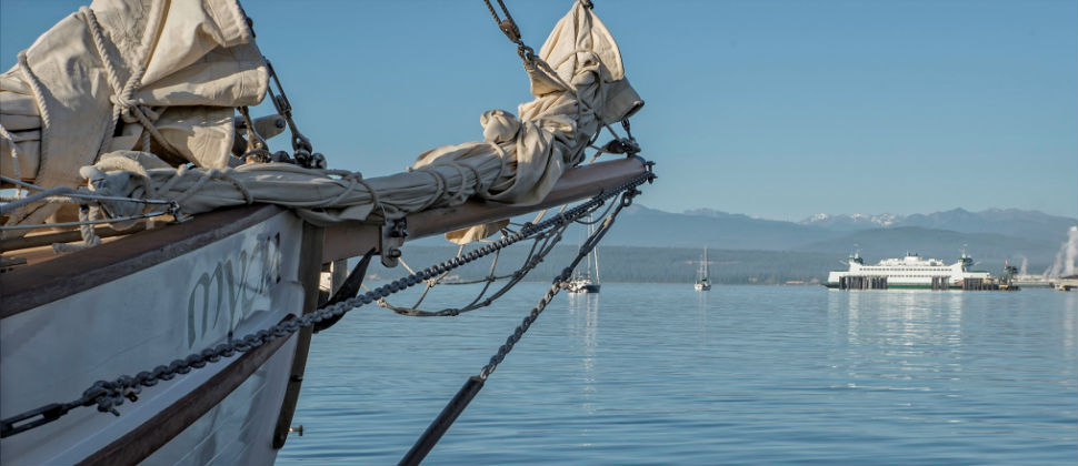 Schooner Mycia docked in the blue waters of Port Townsend Bay with an iconic WA Ferry and majestic Olympic Mountains