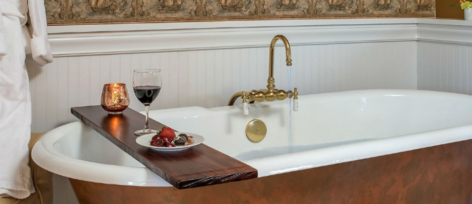 Beautiful claw-foot tub spanned by decorative wooden plank shelf with candle, wine & local chocolates
