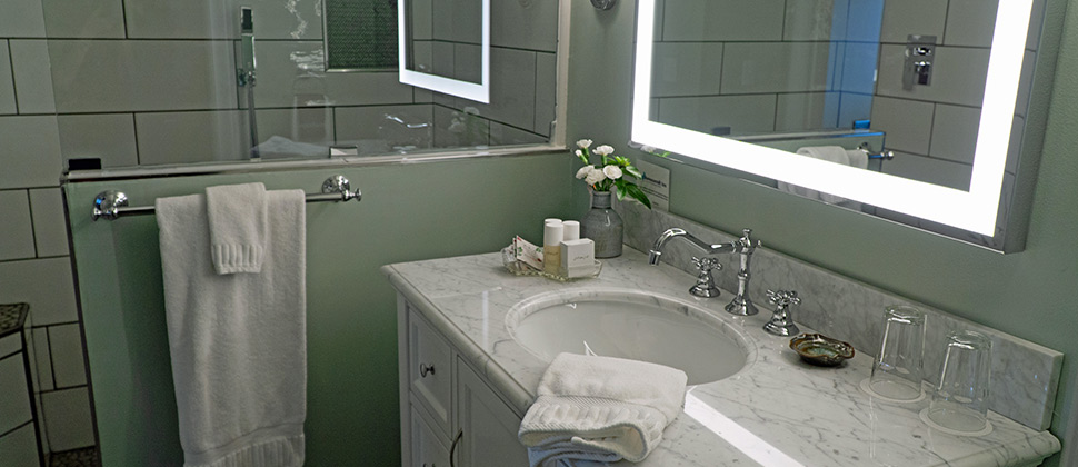 Bathroom with lighted mirror above sink and complimenting mirror to the side.