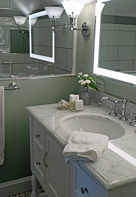 What counter top sink underneath multiple mirrors.