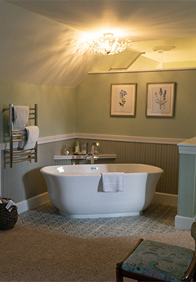 Tub in corner with towerl rack and artwork on walls.